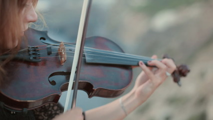 Beautiful violinist plays outdoors