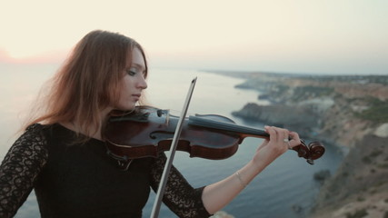 Violinist stands on the cliff on the sea and plays