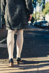 The legs of a woman walking in the street