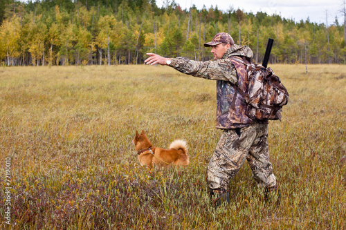 Papiers peints Chasse hunter with dog on the swamp