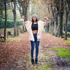 Happy young woman outdoors in a park in autumn.