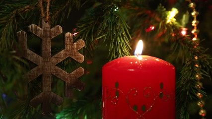 Christmas decoration - candle and wooden snowflake on fir