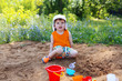 lovely little boy playing with sand on playground
