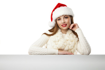 Christmas woman in santa hat pointing empty board