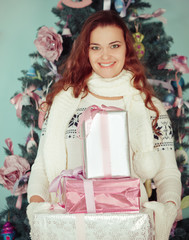 Young happy woman holding Christmas presents