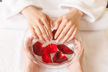 Woman hands in glass bowl with water on white towel.
