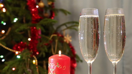glasses with champagne and candle against christmas tree backgro