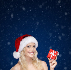 Woman in Christmas cap hands present wrapped with red paper