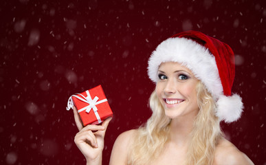 Woman in Christmas cap hands present, on snowy background