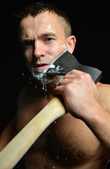 Bearded young man shaving with big axe foam and water splashes