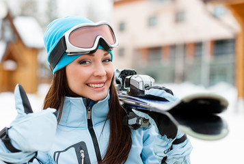 Close up of female who hands skis and thumbs up