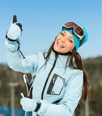 Half-length portrait of female downhill skier thumbing up