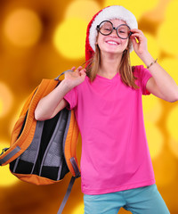 girl  with Santa Claus red hat, backpack and glasses on bright