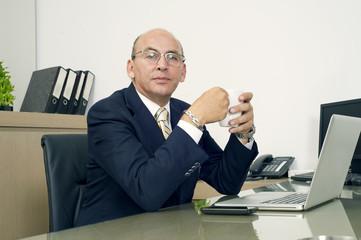Senior Businessman in formalwear drinking coffee in office