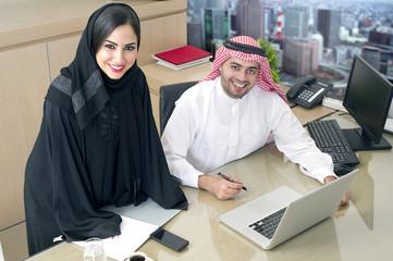 Arabian businessman & arabian Secretary working on laptop