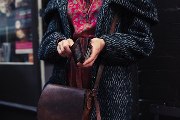 Woman holding her wallet in the street