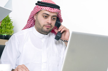 Arabian Businessman using Laptop and talking on phone