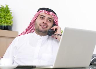 Arabian Businessman using Laptop and talking on phone