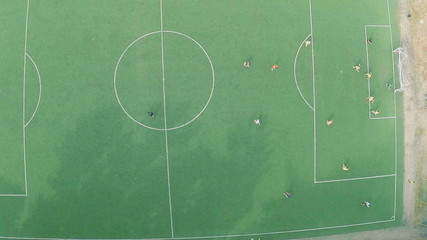 Professional footballers playing match on field, view from above