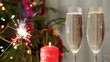 glasses with champagne, candle and sparkler against christmas tr