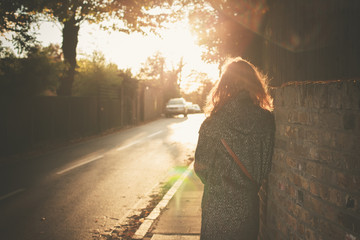 Young woman walking into sunset in city