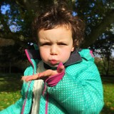 child blowing leafs