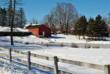 A Snowy Barn on a Farm with a Wooden Fence