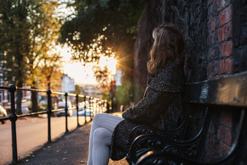 Young woman sitting on bench at sunset