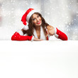 Girl dressed for Christmas showing a blank board