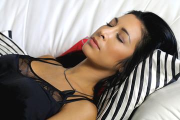 beautiful young woman sleeps on a white sofa