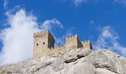 The tower of the ancient castle on a blue sky background