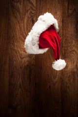 Santa hat hanging on a wooden surface
