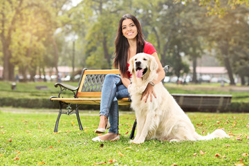 Young girl sitting in a park with her dog