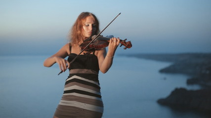 Girl plays violin staying near the beautiful evening sea