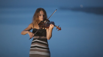Beautiful girl with concentration playing the violin standing on