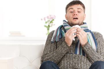 Man blowing his nose in his living room.