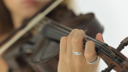 Close up of beautiful girl playing the violin masterfully