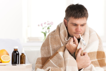 Man with cold sitting on sofa with thermometer in mouth