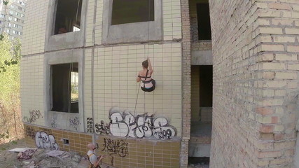 Young people climbing the wall of abandoned building, sport