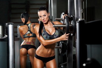 athletic young sexy girl sets weight on barbell in the gym © satyrenko