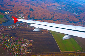 Wing of airplane flying above the fields