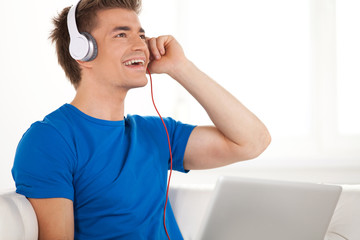 Happy man in headphones with laptop relaxing on sofa at home
