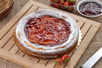 Pastel de fresas y mermelada en ambiente rústico.