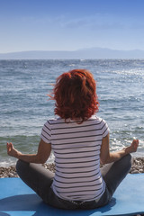 Woman performing joga on sea coast, on windy sunny day