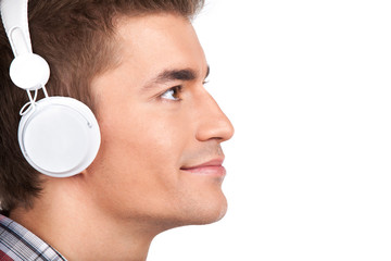 Young man listening headphones on white background.