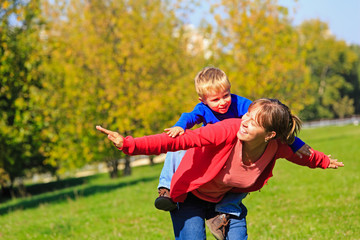 mother and son flying in autumn park