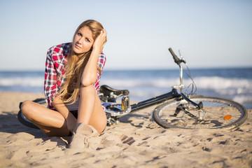 girl sitting next to bike on the beach