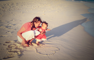 mother and little daughter fun on the beach