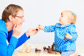 little daughter playing chess with father