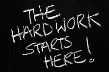 The Hard Work Starts Here written on a blackboard